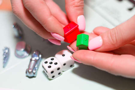 Female hands holding gaming chips, houses and dice close-up Archivio Fotografico