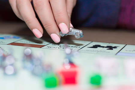 Female hands holding gaming chips, houses and dice close-up.