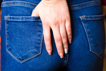 Female hand climbs into the pocket of jeans on the ass