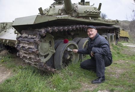 The veteran repairs the tank Stock Photo