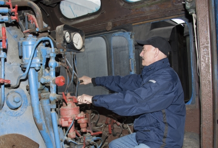 The machinist operates a steam locomotive photo