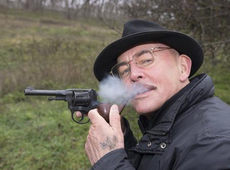 Man with gun  system Nagan smoking his pipe