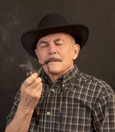 candid: Cowboy in hat with Pipe Stock Photo