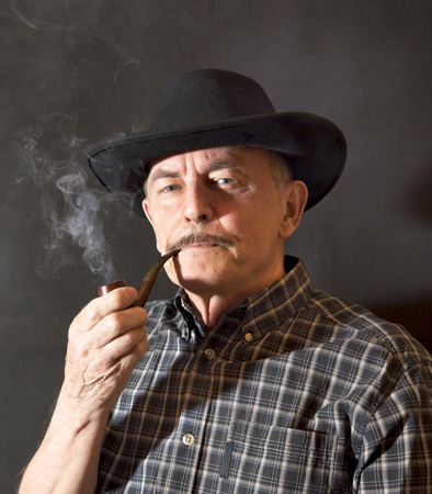Cowboy in hat with Pipe Stock Photo