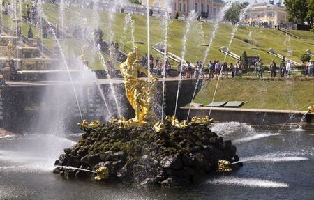 defeated: Peterhof, Saint-Petersburg, Russia - July 6,2015:Tourists admire the fountainSamson tearing the lions mouth.Leo was associated with the defeated King Carl XII, and Samson winner - Peter I.The first sculpture was created by the sculptor C. Rastrelli. Editorial
