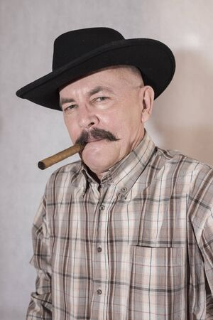 cigar smoking man: The cowboy with mustache, in a black hat smoking a cigar Stock Photo