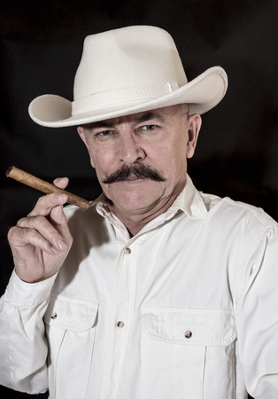 senior adult man: The cowboy with mustache in a white hat, smoking a cigar