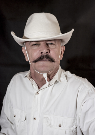 hillbilly: The cowboy with mustache in a white hat Stock Photo