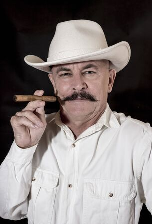 cigar smoking man: The cowboy with mustache in a white hat, smoking a cigar