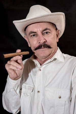 smoking a cigar: The cowboy with mustache in a white hat, smoking a cigar