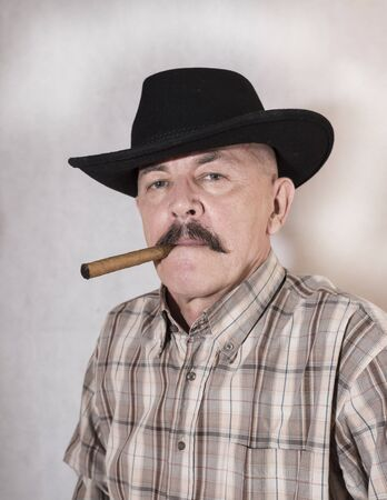 smoking a cigar: The cowboy with mustache, in a black hat smoking a cigar Stock Photo