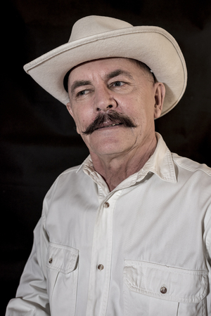 senior adult man: The cowboy with mustache in a white hat Stock Photo
