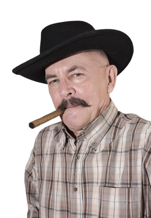 senior adult man: The cowboy with mustache, in a black hat smoking a cigar Stock Photo