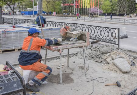 tile cutter: ROSTOV-ON-DON, RUSSIA- APRIL 24- Worker cuts paving tiles on the machine tool on April 24,2016 in Rostov-on-Don