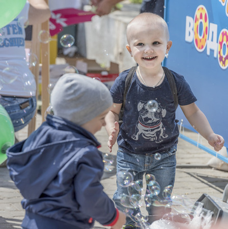 facilitator: Rostov-on-Don, Russia- May 22,2016: Boy catches soap bubbles on holiday