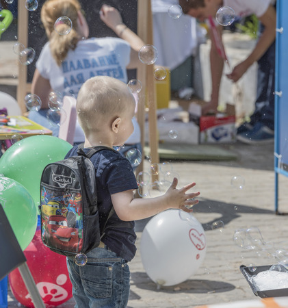 Rostov-on-Don, Russia- May 22,2016: Boy catches soap bubbles on holiday