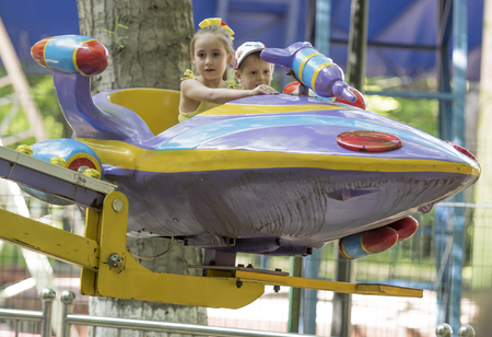 go for: Rostov-on-Don, Russia- May 29,2016: Boy and girl with admiration go for a drive on the carousel in the park named after Ostrovsky