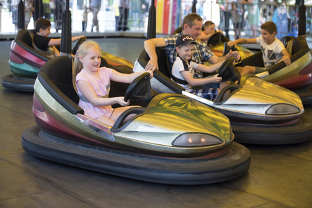 steers: Rostov-on-Don, Russia- June 13: Girl and boy with Dad ride attraction Circuit in amusement park