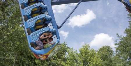 Rostov-on-Don, Russia- June 13: Brave citizens ride the attraction Kamikaze in amusement park Editorial