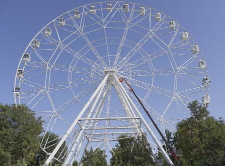 meters: Rostov-on-Don, Russia- July 16:Construction of the Ferris wheel 65 meters. The workers, while being on a mounting rig, collecting wheel