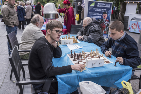 pawn adult: Moscow, Russia -September 09,2016: Men play chess in the park Muzeon. In the background, people make purchases at the fair