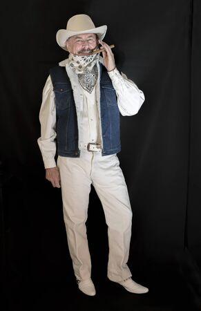El vaquero con bigote en un sombrero blanco, fuma un cigarro Foto de archivo