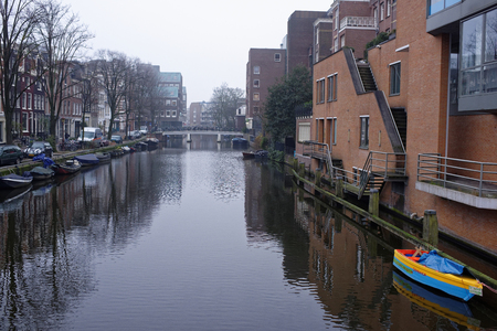 Amsterdam, Nederland- December 30,2016: Along the canal walk citizens and moving vehicles Stock Photo