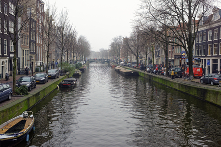 Amsterdam, Nederland- December 30,2016: Along the canal walk citizens and moving vehicles Redactioneel