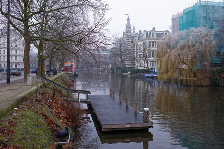 amstel river: Amsterdam, Nederland- December 30,2016: Along the canal walk citizens and moving vehicles Stock Photo
