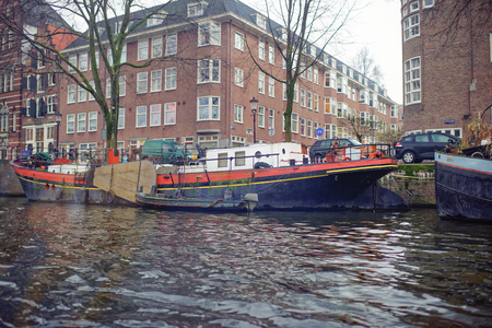 Amsterdam, Nederland- December 30,2016: Along the canal walk citizens and moving vehicles Editorial