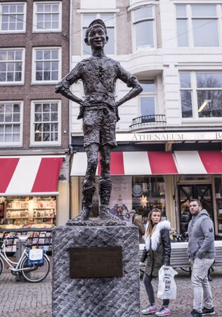 glint: Amsterdam,Netherlands-December 30,2016:Spui Square.Het Amsterdamse Lieverdje (the Little Amsterdam Darling).He�s got a rascally glint in his eye and a mischievous, impish grin