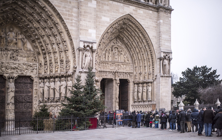 Paris, France- January 01,2017:Tourists stand in line at the Cathedral of Notre Dame, some walking