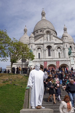 mimo: Paris,France-April 30, 2017:Tourists walk,relax and take pictures near the Basilica Sakre-Coeur.There is a living statue on the pedestal Editorial