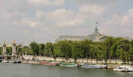 Paris,France- April 29, 2017: View of the embankment of Por de Sham Elise and the Grand Palace. On the waterfront are pedestrians