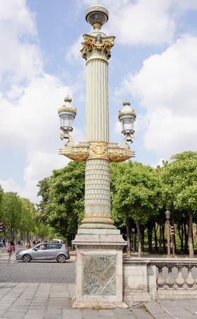Paris, France - April 29, 2017: Rostral column with lanterns on the Place de la Concorde. By area moving pedestrians and cars