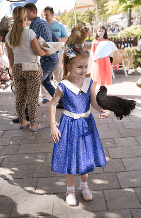 Rostov-on-Don, Russia- September 16,2017: Girl with tame birds. Nearby there are participants of an attraction Editorial