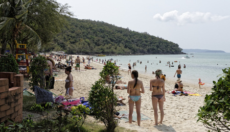 Pattaya,Thailand- February 20,2018: Sai Kaew Beach -Military Beach.People sunbathe and swim.Some vacationers stroll along the shore.In the foreground the girls are discussing something