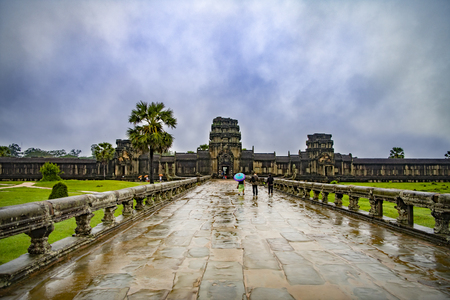 Angkor Wat,Cambodia-September 04, 2019: Angkor Wat-largest temple in the world. It is raining. Tourists walk around the temple