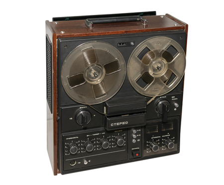 Reel stereo tape recorder, made in 1983, isolated on white (inscriptions: stereo, off, volume, timbre, stop, start, recording level)