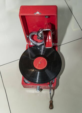 Portable vintage record player in a red body with a plate