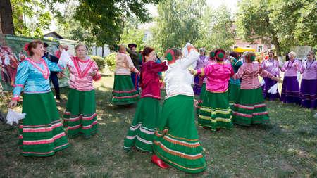 Starocherkasskaya,Rostov Region, Russia- July 26,2014:Cossack family dancing on the lawn in the village under music played Cossack Choir