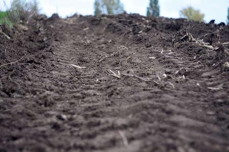 Tracks of heavy tractor on plowed field