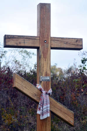 Big wooden christian cross standing in park in autumn