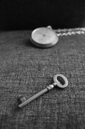 Old key and watch on grey texture