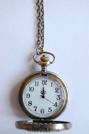 Old golden pocket watch showing twelve o clock