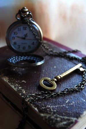 Vintage Key, Book and Pocket Watch  The Key is in Time Stock Photo
