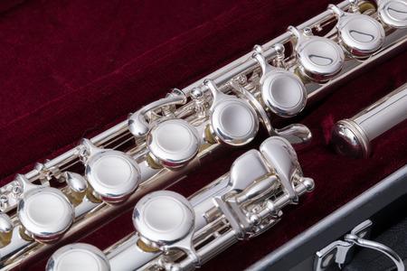 Silver flute in the red velvet case photo