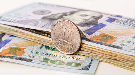 burning money: US Currency with one quarter coin sitting on one hundred dollar note Stock Photo