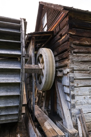 Photo of old watermill building with cracked planks.