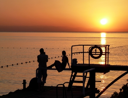 At sunrise. Summer. Romantic date on the beach. Memory photo in backlighting against the sea and the rising sun.